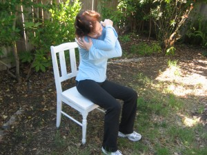 Side bend by lifting the right side of your pelvis off the chair and tilting your head to the right